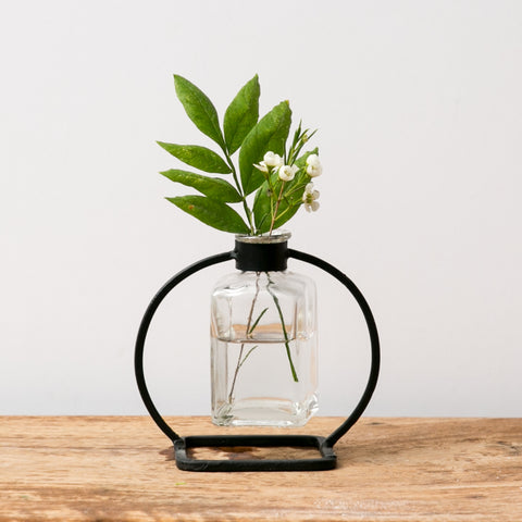 black metal scientific stand and glass bud vase