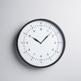 black metal wall clock with white face