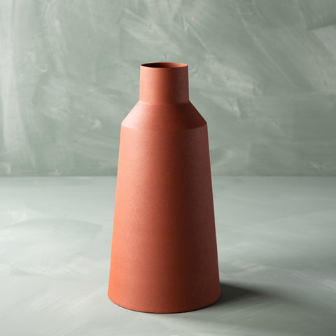large rust colored metal vase