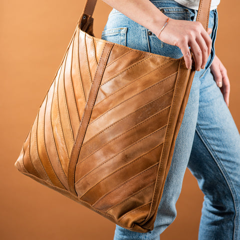brown leather crossbody purse with herringbone stitching pattern