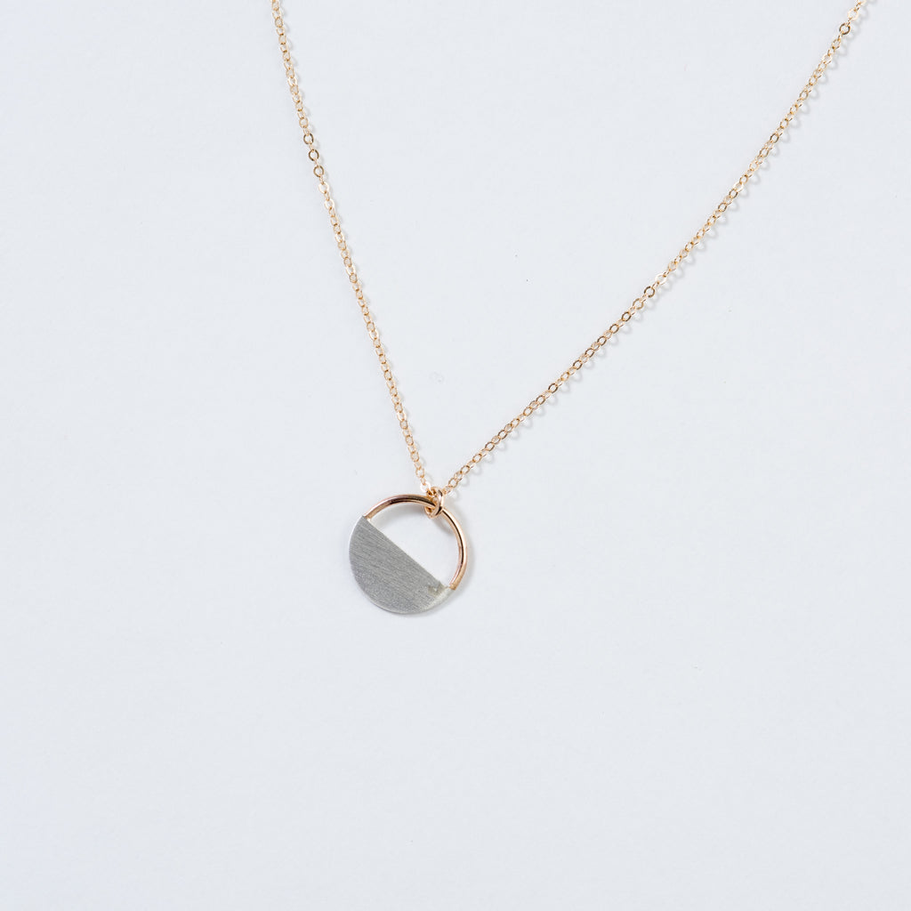 gold necklace with silver and gold half-moon charm