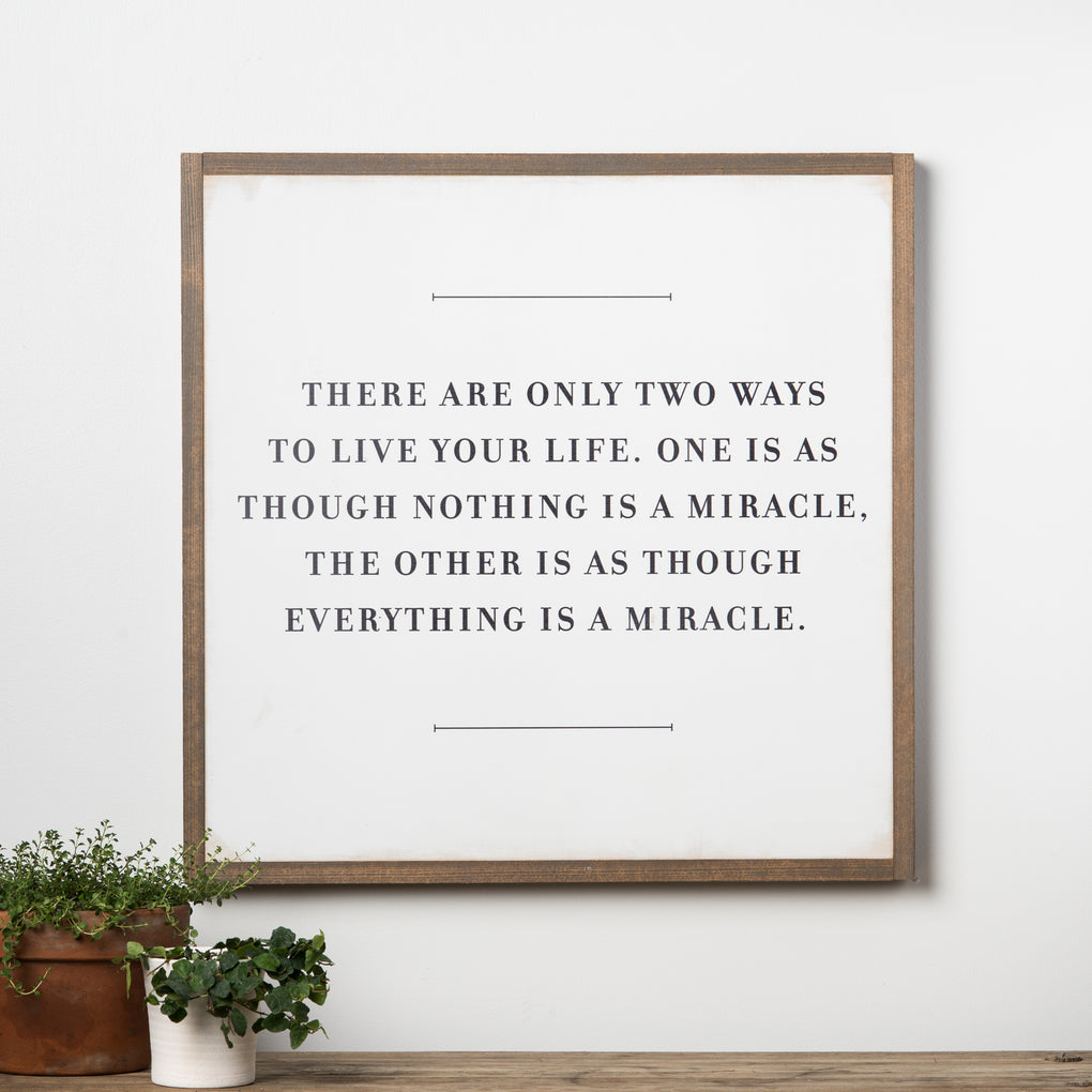 "white wooden quote sign that reads ""there are only two ways to live your life. one is as though nothing is a miracle, the other is as though everything is a miracle""."