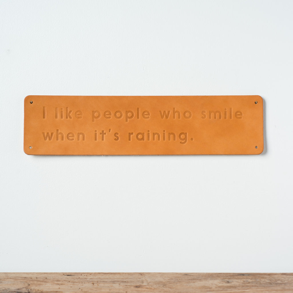 "leather quote sign reading ""i like people that smile when it's raining"""