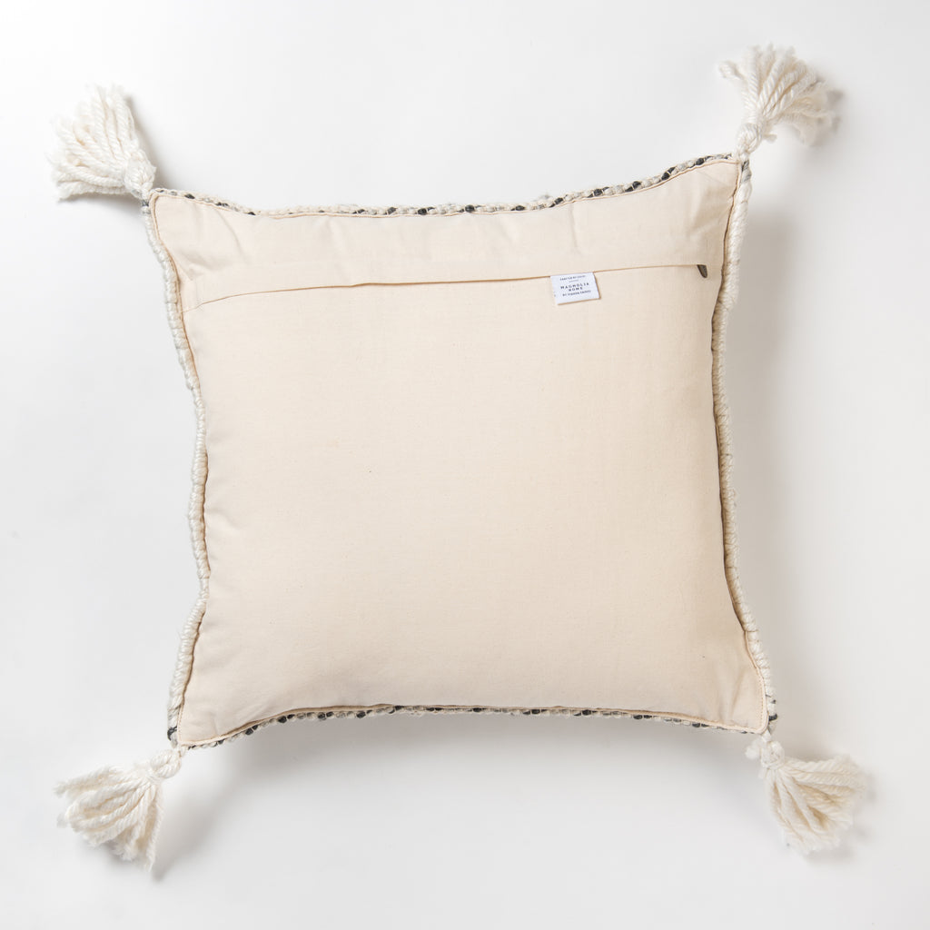 white textured square pillow with diamond pattern and tassels