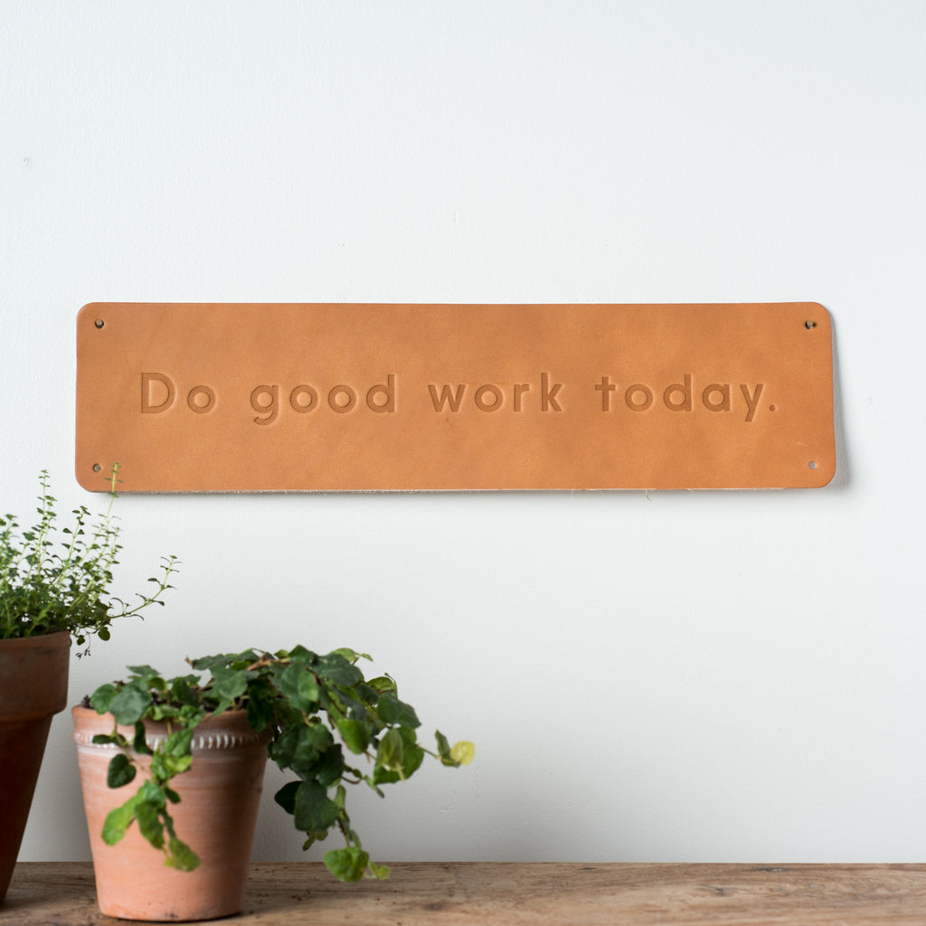 "leather quote sign with debossed phrase reading ""do good work"""