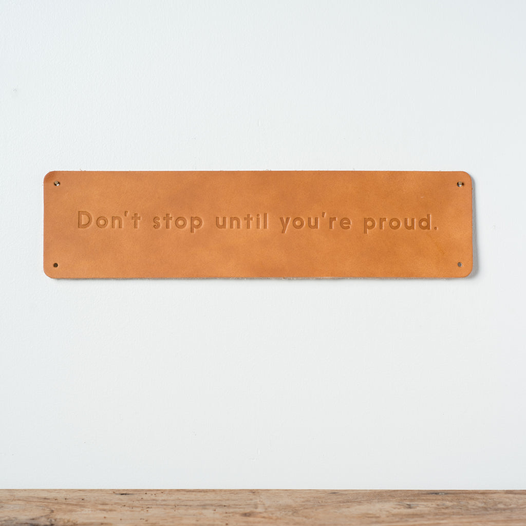 "leather quote sign that reads ""don't stop until you're proud."""