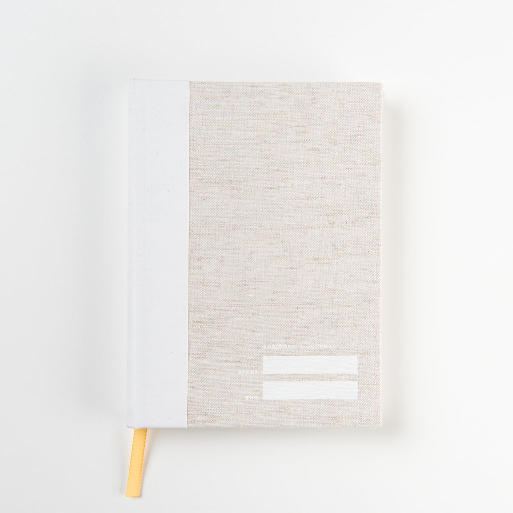 oatmeal colored journal with white binding