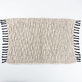 Black and white bath mat with tassels