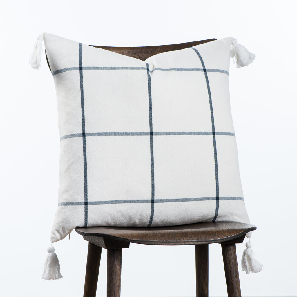 white and navy throw pillow with navy grid line pattern and white tassels