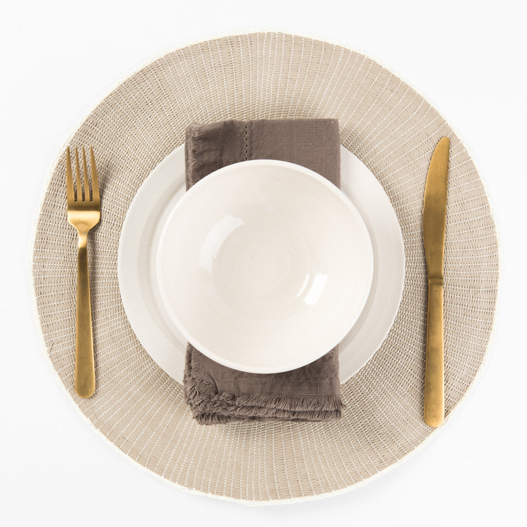 Round taupe placemat with plate and silverware