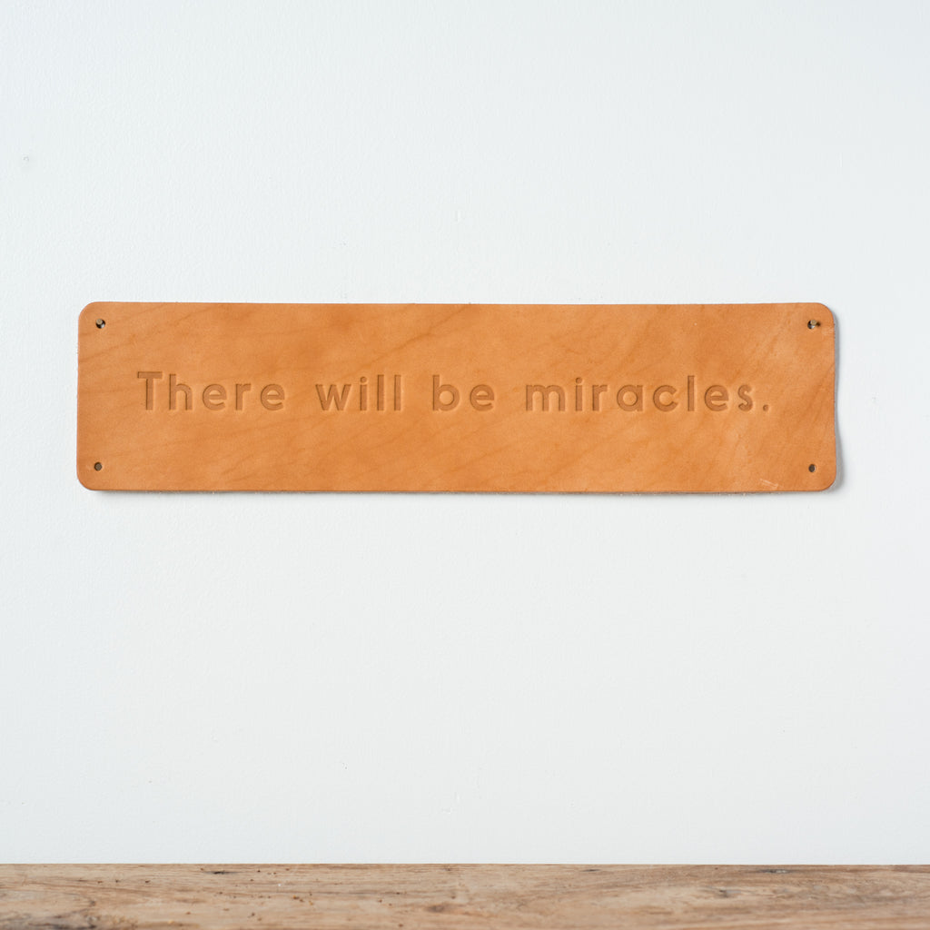 "leather quote sign with debossed phrase reading ""there will be miracles"""