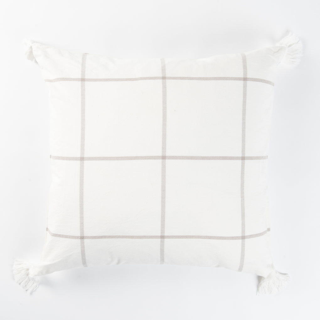 white and gray throw pillow with navy grid line pattern and white tassels
