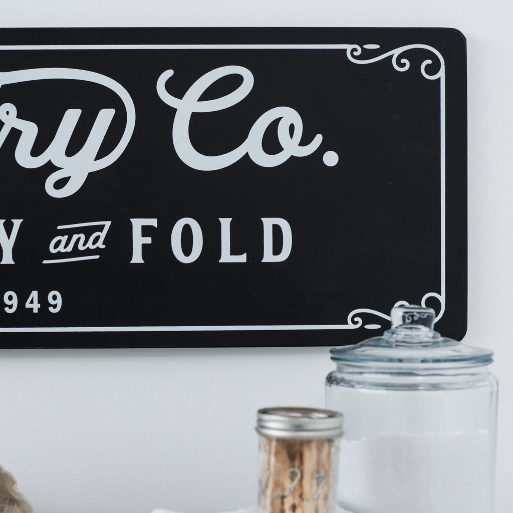"black wall sign that reads ""Laundry Co. Wash, dry and fold"""