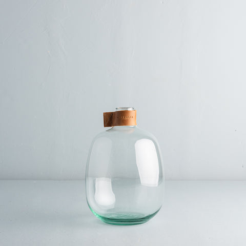 small clear glass bubble vase with leather collar that has magnolia logo embossed on it