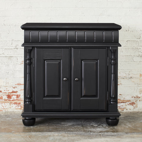 traditional wooden bedside chest with turned detail and black finish