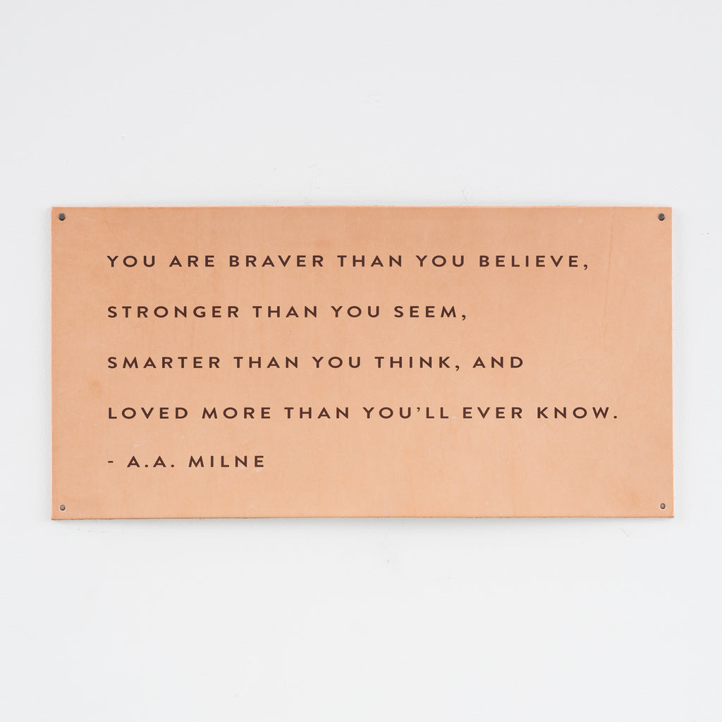 leather wall sign with a quote by a.a. milne