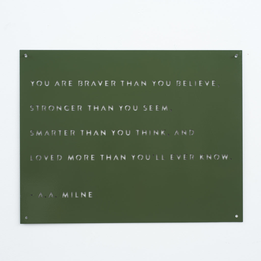 green metal sign with quote by a.a. milne