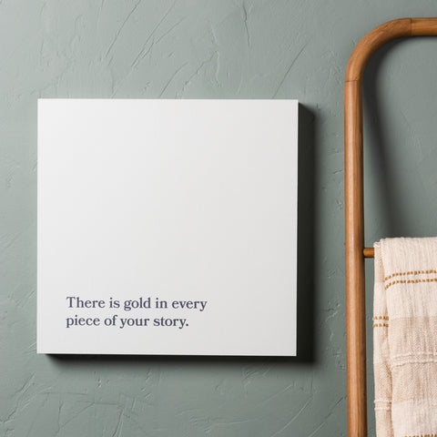 "light sage green wooden sign with quote ""There is gold in every piece of your story."" in dark green serif font"