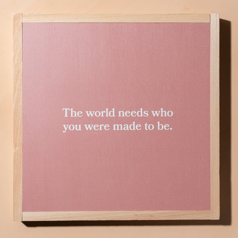 "blush pink wooden sign with quote ""the world needs who you were made to be"" in white with natural wood border"
