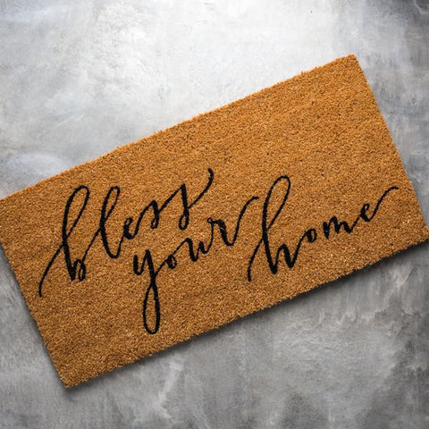"jute doormat that says ""bless your home"" in script lettering"