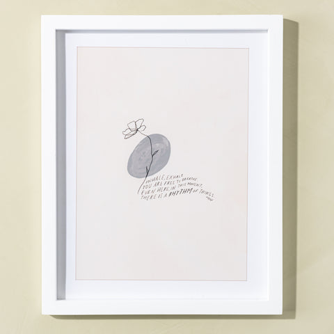 "white framed art print with flower and quote saying ""inhale, exhale, you are free to breathe. even here. in this moment. there is a rhythm of things. - MHN"""