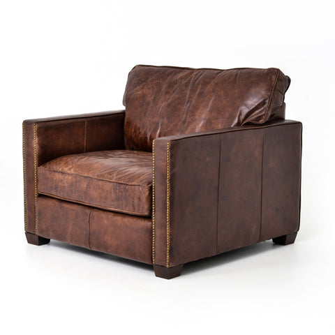 medium brown leather arm chair with nailhead arms