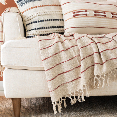 beige linen colored throw blanket with small spice red stripes with tassel fringe