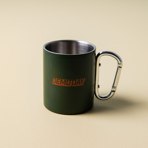 "green stainless steel mug with ""demoday"" printed on the side with silver carabiner handle"