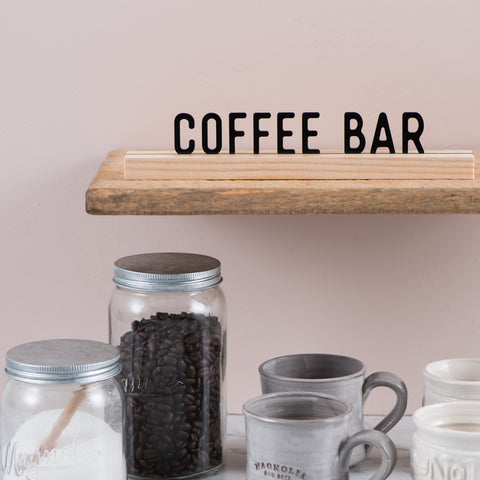 "acrylic sign that reads ""coffee bar"" with wooden stand"