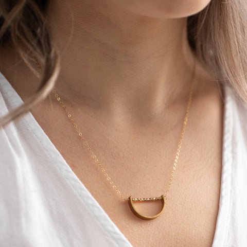 gold necklace with gold half circle outline pendant