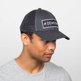 dark grey snap adjustable trucker hat with #demoday patch on front
