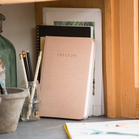 "blush pink linen journal with gold lettering reading ""FREEDOM"""