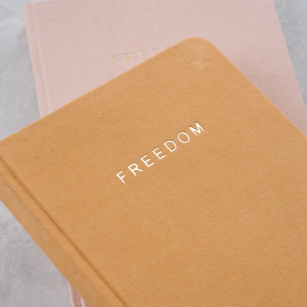 "gold hardcover journal with embossing that reads ""FREEDOM"""