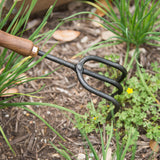 black metal gardening cultivator with wooden handle