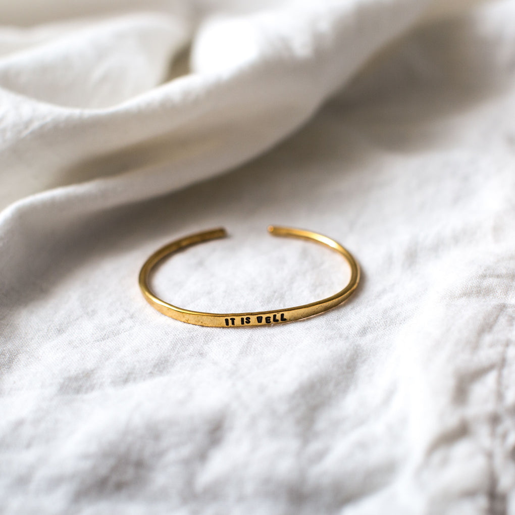 "brass bracelet with stamped phrase in band reading ""it is well"""