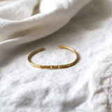 "brass bracelet with stamped phrase in band reading ""courage dear heart"""