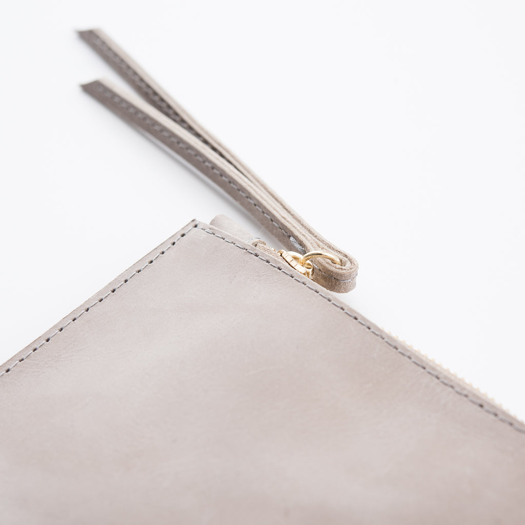 grey leather clutch with tasseled zipper