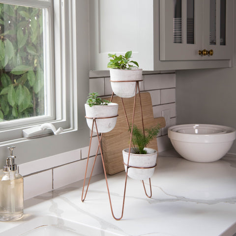 three white modern ceramic pots with thin copper stand