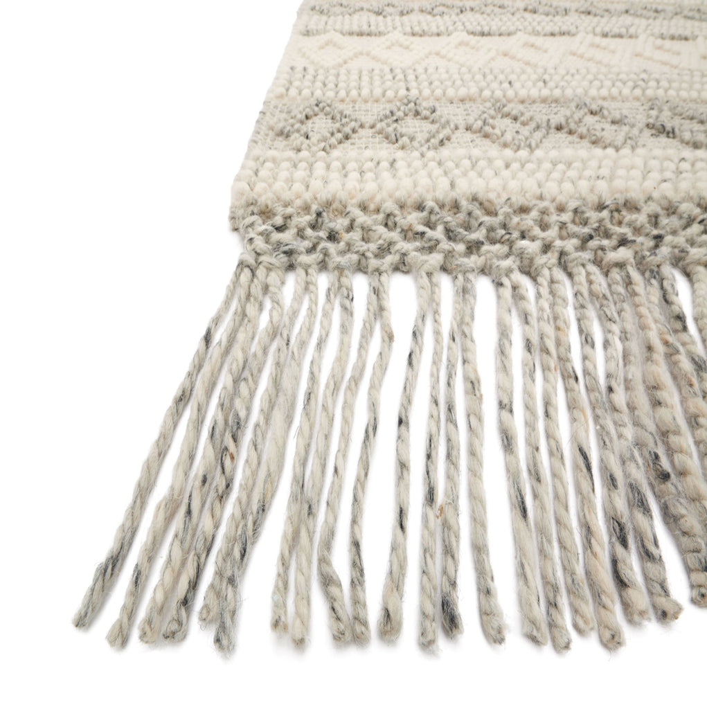 modern grey and white diamond pattern rug with grey tassels