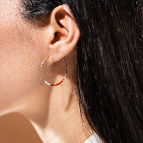 gold-fill hoop earrings with white and terracotta colored beads