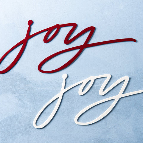 "red powder-coated metal script wall sign that reads ""joy"""
