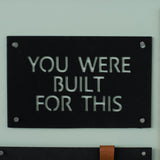 "black metal quote sign that reads ""you were built for this"""