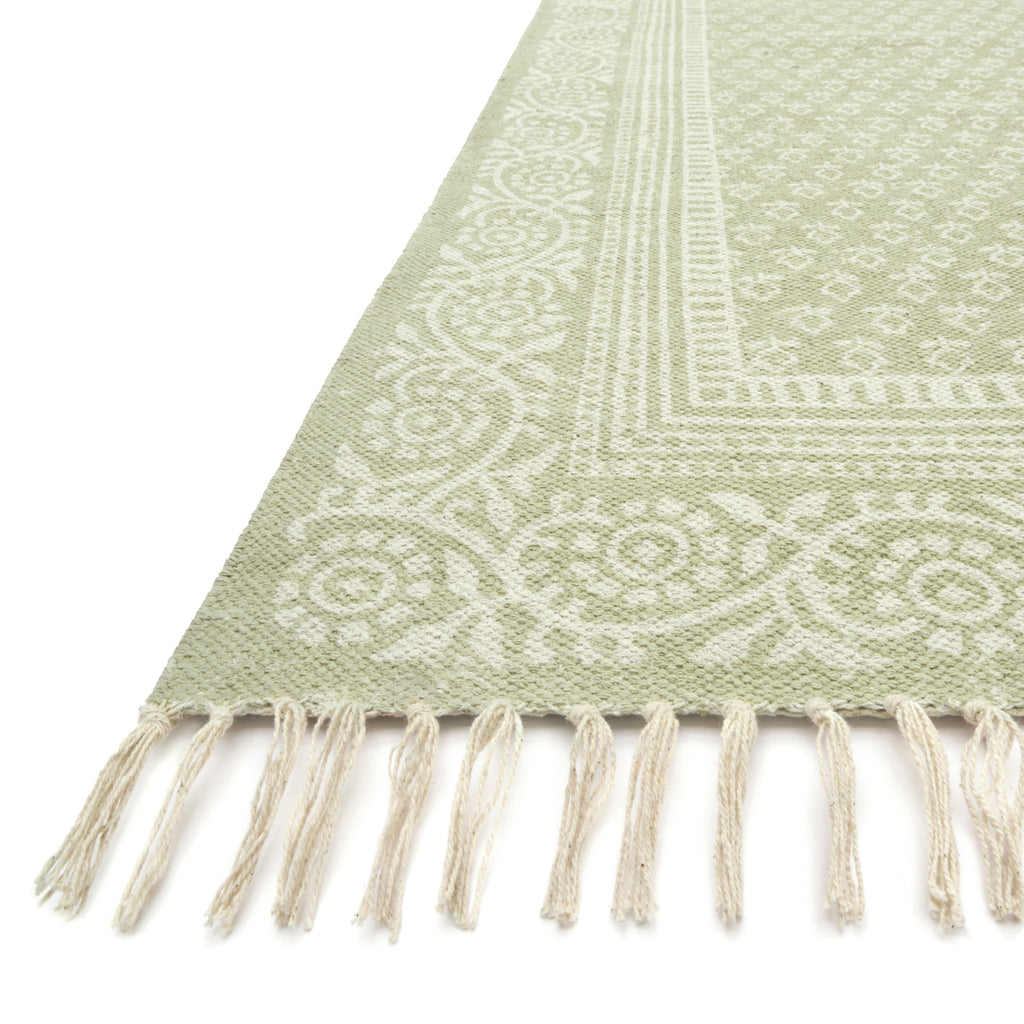 modern light green rug with ivory detail and tassels