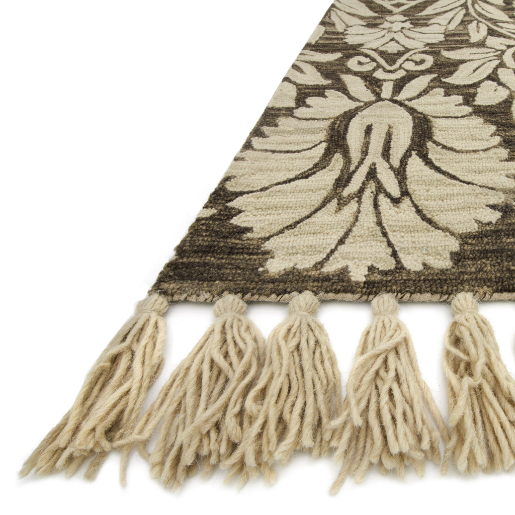 charcoal grey rug with large tan floral detail and tassels