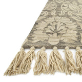 grey rug with large light tan floral detail and tassels
