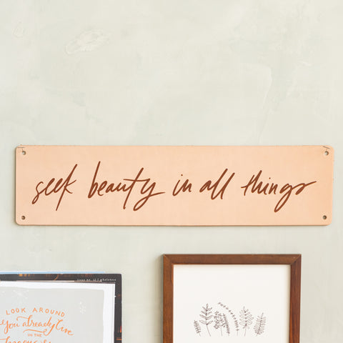 "light colored leather sign that reads ""seek beauty in all things"" in script lettering"