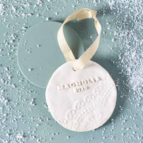 "white ceramic circle christmas ornament with ""Magnolia 2020"" and lace detail"