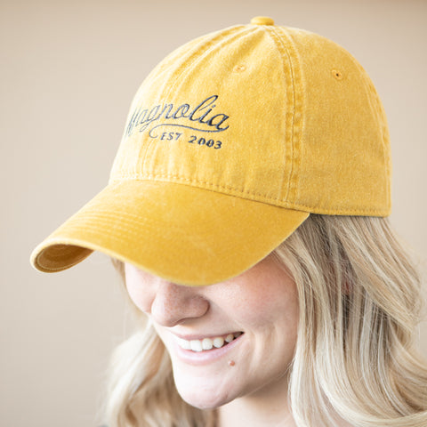 "yellow ball cap with ""Magnolia Est 2003"" in cursive script"
