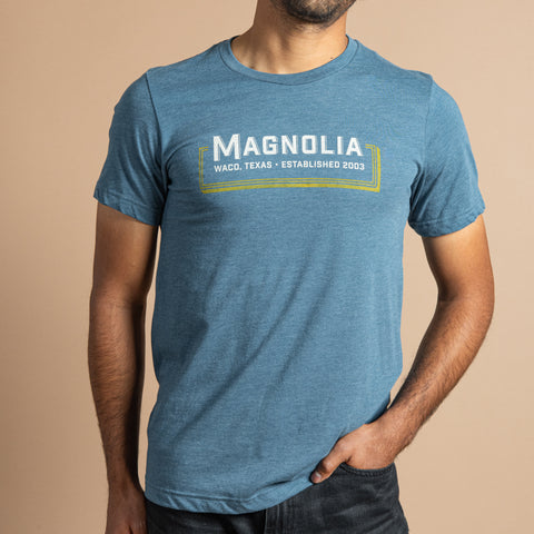 "blue t-shirt with retro graphic reading ""magnolia, waco, texas, established 2003"" in white across chest"