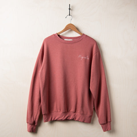 muted rose colored sweatshirt with magnolia script logo in white stitching on left chest
